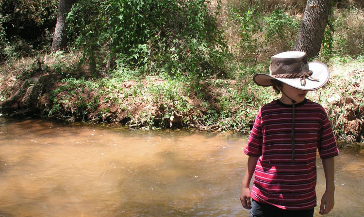 A little girl standing next to a river
