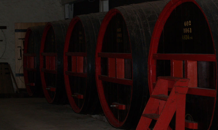 A large red chair in front of a barrel