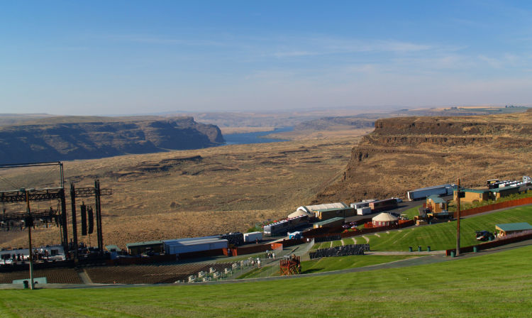 A group of people in a field with Gorge Amphitheatre in the background