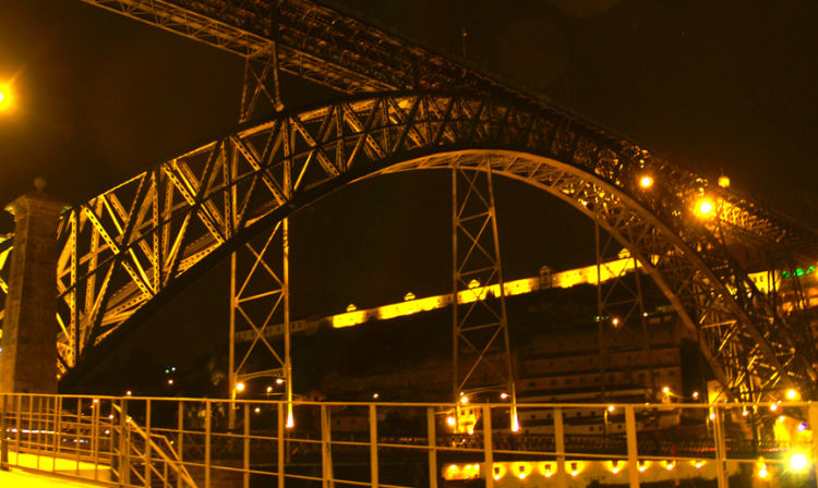 A close up of a train crossing a bridge lit up at night