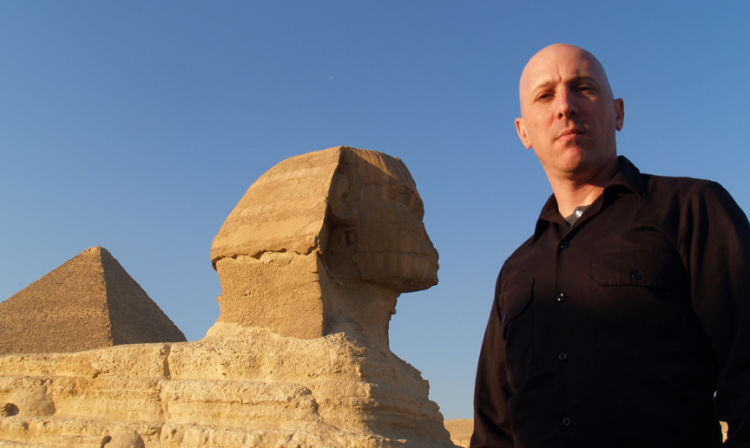 Maynard James Keenan standing in front of a large rock