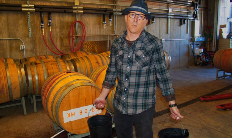 Maynard James Keenan standing in front of a barrel
