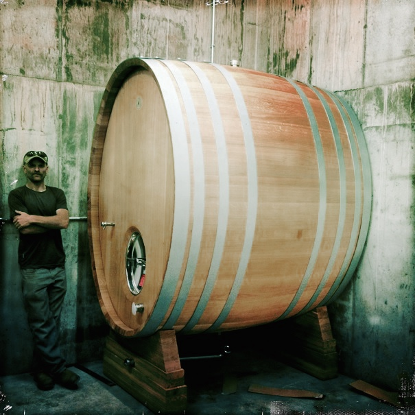A person standing in front of a barrel